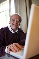 Mature man using laptop, smiling, portrait (focus on man)