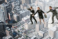 Windswept businessman and woman on tightrope over cityscape