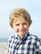 Boy (4-6) on beach, smiling, portrait, close-up