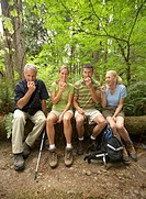 Four adults sitting on log in forest, eating apples