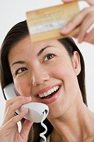 Happy Woman Paying with Credit Card over Telephone