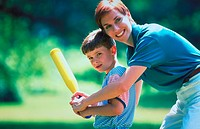 A mother helps her young son swing a baseball bat.