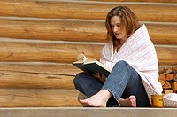 Woman reads a book at the cottage