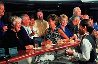 View, from behind the bar, of a smiling and laughing crowd standing and sitting with drinks at a restaurant bar.