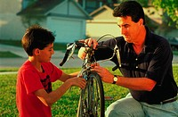 A father and son working outside together to repair a bicycle