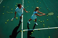 Aerial view of a male tennis instructor and his female student on a tennis court surrounded by tennis balls.