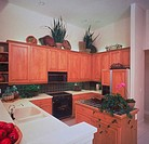 A modern kitchen display with wood cabinets, a refrigerator, stove, microwave oven, sink and white countertops.