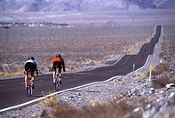 Man and woman bicycling are the only people on a long lonely two-lane road through Death Valley, CA.