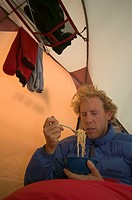 An unhappy man eating noodles in a tent.
