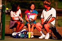 African American woman, Asian woman and caucasian man sitting on bench talking together after playing tennis.
