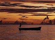 Mascarene Islands, Mauritius, fisherman standing on boat, sunset