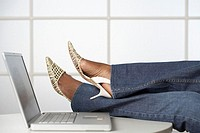 Woman with Her Feet Up on Desk near Laptop