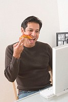 Man sitting by computer eating slice of pizza