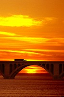 Silhouette of truck on bridge at sunset.  Computer manipulated.