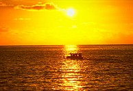 Outrigger canoe on the ocean at sunset, with the sun reflecting in the water, Hawaii, South Pacific.