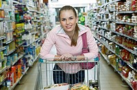 Young woman shopping in supermarket, leaning on trolley, portrait