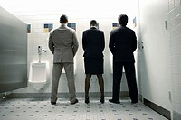 Businesswoman Standing Between Businessman at Urinals