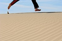 Feet running over sand dune. Death Valley, California. USA
