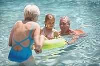 Grandparents Playing with Their Granddaughter in the Pool