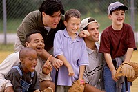 Close-up of three fathers with their sons wearing baseball gloves in a baseball field