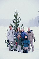 Portrait of a family standing in front of a Christmas tree in snow