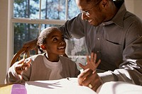 Close-up of a father helping his daughter with her homework