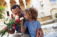 Father holding a bouquet of flowers with his daughter