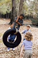 Two boys and two girls playing on a tire swing