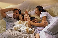 High angle view of parents and their two children playing in bed