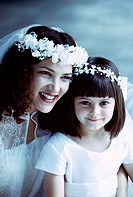 Close-up of a bride sitting with a flower girl