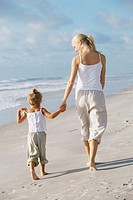 Rear view of a mother walking with her daughter on the beach