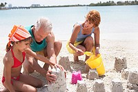 Couple Building Sand Castles With Granddaughter