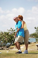 Woman Kissing Man Before Golf Swing