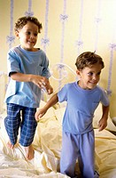 Two boys jumping on the bed