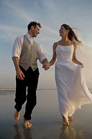 Low angle view of a newlywed couple walking on the beach