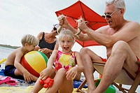 Close-up of a grandfather pulling his granddaughter´s hair on the beach