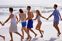 Rear view of young men and young women holding hands running on the beach