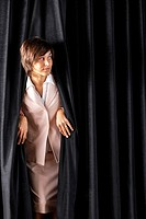 Woman Looking from Behind Theater Curtain