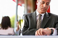 Businessman in Restaurant Checking the Time
