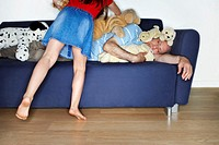Girl Placing Stuffed Animals on Mature Man Sleeping on Couch