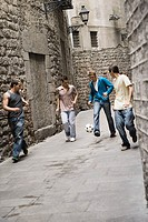 Young Men Practicing Soccer in Street