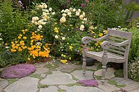 High angle view of an armchair and flowers in a garden