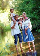 Parents holding son and daughter (4-6), standing in stream