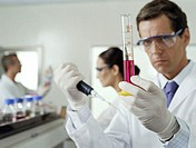Male scientist holding test tube and syringe, colleagues in background