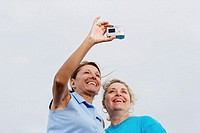 Two mature women taking picture, low angle view, close-up