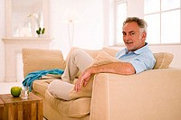 Mature man sitting on sofa in living room, portrait