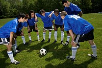 Teenage male (16-20) soccer players in huddle