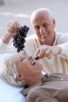 Mature man feeding grapes to woman, laughing