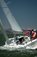 Crew sailing J105 class boat, rear view