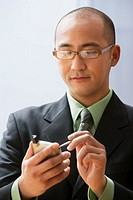 Young businessman using personal digital assistant, close-up